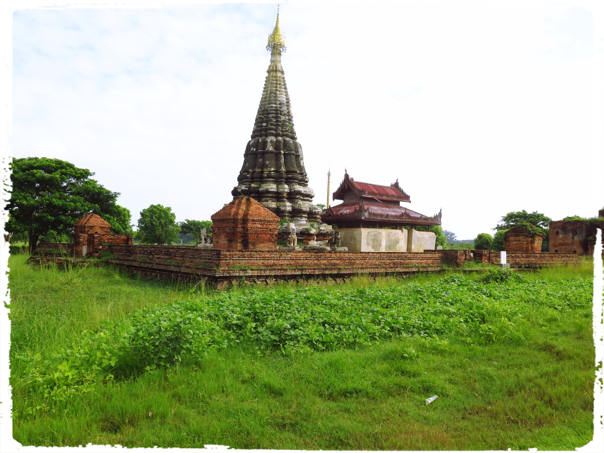 The spired stupa is the Lawka Dawtha Man Aung Pagoda. The Pagoda encloses a small shrine with a statue of Buddha in a small building nearby. The Pagodas house relics but not always one is able to find original relics and house them. Many Pagodas have housed replica of the relics and have drawn the faithful.