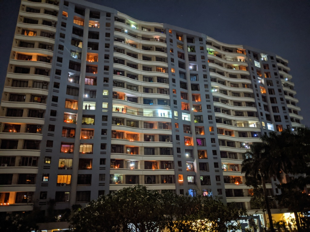 Building with lights switched off and people lighting lamps for 9 minutes