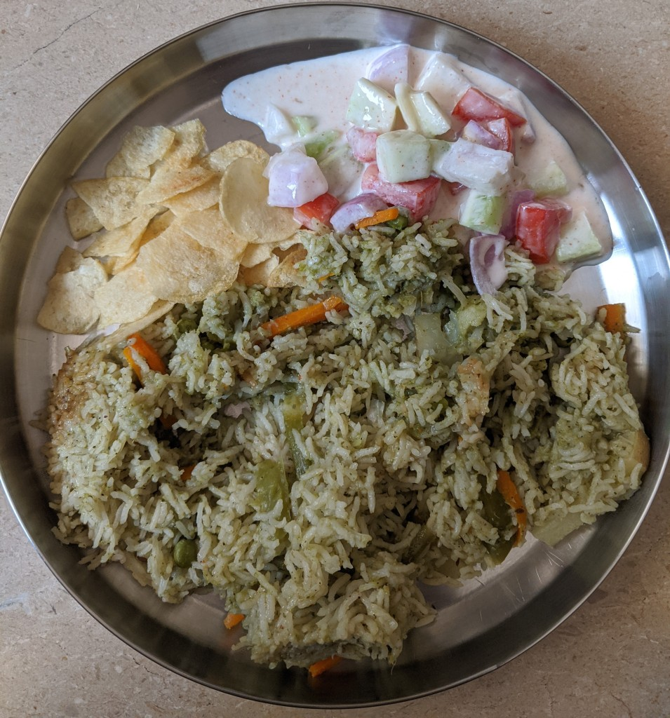 A plate of south indian pulav made with coconut and coriander ground with spices and lots of vegetables along with raita