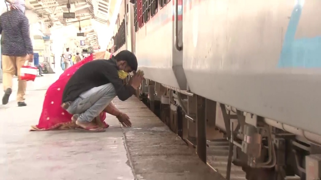 A couple praying before boarding a train back to their hometowns