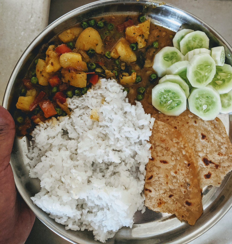 Half a chapati, alu mutter gravy, cucumber slices and some rice