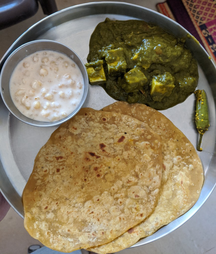 Palak paneer with two chapatis, boondi raita and a chilli pickle